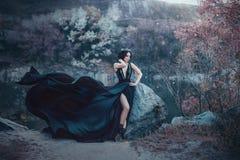 De donkere koningin stelt tegen de achtergrond van sombere rotsen Een luxueuze zwarte kleding met een lange trein die in fladdere Stock Afbeelding