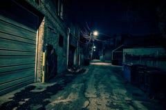 De donkere lege en enge stedelijke steeg van de stadsstraat bij nacht Stock Afbeeldingen