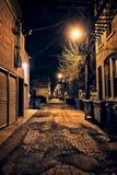 De donkere lege en enge stedelijke steeg van de stadsstraat bij nacht Stock Afbeelding