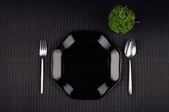 De donkere moderne minimalistic spot van het restaurantmenu omhoog met zwarte glanzende plaat, lepel, vork en groene installatie, Royalty-vrije Stock Foto's