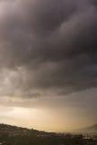 De donkere onweerswolken verzamelen zich over een brede vallei Stock Foto's