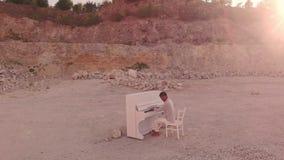 De donkere piano van mensenspelen in bergen onder stenen Onwerkelijk verhaal stock video