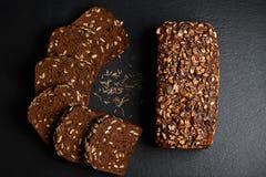 De donkere rogge, graangewassenbrood met zonnebloemzaden, geheel brood, korrels van komijn op een donkere achtergrondschalieraad, Stock Foto's