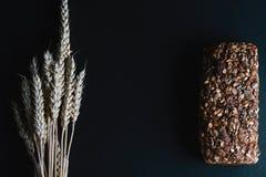 De donkere rogge, graangewassenbrood met zonnebloemzaden, geheel brood, tarwestammen op een donkere schalie als achtergrond schee Royalty-vrije Stock Afbeelding