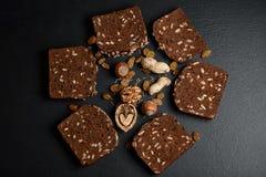 De donkere rogge, graangewassenbrood met zonnebloemzaden, korrels van komijn, noten, rozijnen op een donkere schalie als achtergr Stock Afbeelding