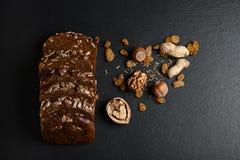 De donkere rogge, graangewassenbrood met zonnebloemzaden, korrels van komijn, noten, rozijnen op een donkere schalie als achtergr Royalty-vrije Stock Foto