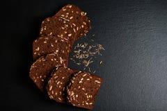 De donkere rogge, graangewassenbrood met zonnebloemzaden, korrels van komijn op een donkere schalie als achtergrond scheept, conc Royalty-vrije Stock Afbeelding
