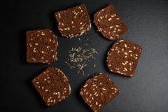 De donkere rogge, graangewassenbrood met zonnebloemzaden, korrels van komijn op een donkere schalie als achtergrond scheept in, o Royalty-vrije Stock Foto