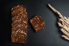 De donkere rogge, graangewassenbrood met zonnebloemzaden, tarwevlokken op een donkere schalie als achtergrond scheept, concept he Stock Foto's