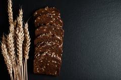 De donkere rogge, graangewassenbrood met zonnebloemzaden, tarwevlokken op een donkere schalie als achtergrond scheept, concept he Stock Foto