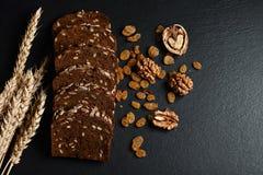 De donkere rogge, graangewassenbrood met zonnebloemzaden, verspreidde rozijnen, noten, tarwevlokken op een donkere achtergrondsch Stock Foto