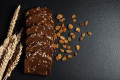 De donkere rogge, graangewassenbrood met zonnebloemzaden, verspreidde rozijnen, tarwevlokken op een donkere achtergrondschalieraa Stock Afbeelding