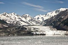 De donkere rotsachtige gletsjer glijdt in de oceaan. Stock Afbeelding