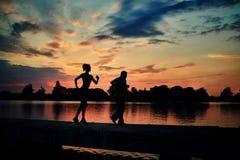 De donkere silhouetten van rennen agenten terwijl zonsondergang dichtbij meer weg Stock Afbeeldingen