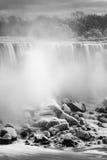 De donkere sneeuw behandelde rotsen bij de bodem van een grote waterval, mist Royalty-vrije Stock Fotografie