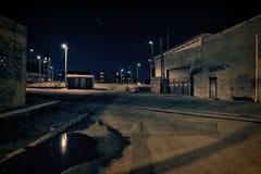 De donkere steeg van het fabriekspakhuis met spoorwegsporen Stock Foto