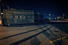 De donkere steeg van het fabriekspakhuis met spoorwegsporen bij nacht Stock Fotografie