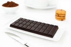 De donkere tablet van de chocolade, cacao, koekjes witte lijst Stock Afbeeldingen