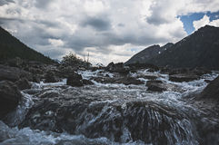 De donkere vallei van de mistroostigheidsberg langs de bergrivier Stock Fotografie