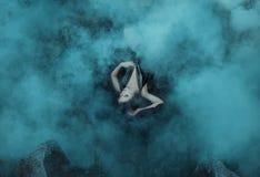 De donkere vampierkoningin ligt in de greep van de mist op haar zwarte kleding met een diepe halslijn Het meisje is binnen gewikk Stock Foto