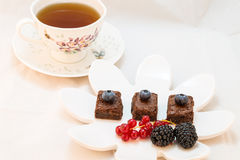 De donkere vierkanten van de chocoladebrownie met gemengde bessen en kop thee Stock Fotografie