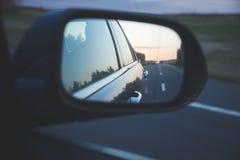 De donkere wegbezinning met asfaltlijnen boven de zonsondergang aan kant weerspiegelt achtermening van het bewegen van auto Stock Foto's