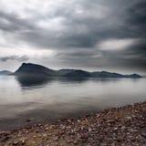 De donkere wolken van het onweer over het eiland in overzees Stock Afbeeldingen