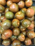 De donkergroene achtergrond van kumatotomaten, Gezond voedselconcept Stock Afbeeldingen