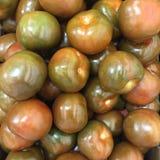 De donkergroene achtergrond van kumatotomaten, Gezond voedselconcept Royalty-vrije Stock Foto