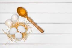 De dooier vrouwelijke hand van de eieren houten lepel Royalty-vrije Stock Afbeeldingen