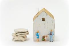De doopvont wit huis van de Minatuefamilie en stapel van muntstukken Stock Foto