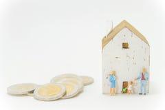 De doopvont wit huis van de Minatuefamilie en stapel van muntstukken Stock Fotografie