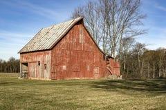 De doorstane rode schuur is een plattelandsgebied Stock Afbeeldingen