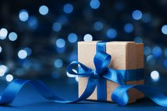 De doos of het heden van de vakantiegift met booglint tegen blauwe bokehachtergrond De magische kaart van de Kerstmisgroet