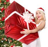 De doos van de de holdingsgift van het meisje door Kerstmisboom. Stock Afbeeldingen