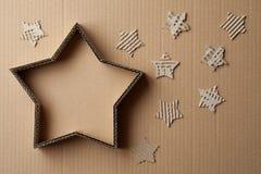 De doos van de Kerstmisgift in de vorm van een ster, door decoratie, op kartonachtergrond die wordt omringd Stock Afbeeldingen
