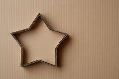 De doos van de Kerstmisgift in de vorm van een ster op een kartonachtergrond Stock Afbeeldingen