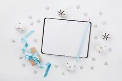 De doos van de Kerstmisgift met blauw hierboven lint, lege notitieboekje en kenwijsjeklok op wit bureau De groetkaart van de vaka Stock Afbeeldingen