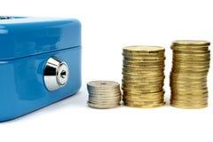 De doos van het contante geld met slot en gestapelde muntstukken Stock Afbeelding