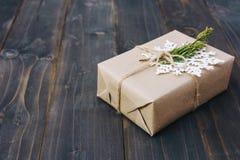 De doos van de Kerstmisgift en witte sneeuwvlokken op houten planken wordt geplaatst die stock afbeelding