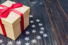 De doos van de Kerstmisgift en witte sneeuwvlokken op houten planken wordt geplaatst die royalty-vrije stock foto's