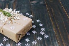 De doos van de Kerstmisgift en witte sneeuwvlokken op houten planken wordt geplaatst die royalty-vrije stock foto
