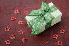 De doos van de Kerstmisgift met groen lint op een rode doek stock afbeelding