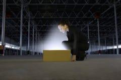 De Doos van onderneemsterlooking at glowing in Leeg Pakhuis stock foto