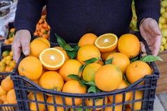 De doos van rijpe sinaasappelen in de handen van verkoper bij plantaardige vruchten winkelt royalty-vrije stock foto's