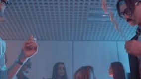 De Dorkybeambten in reusachtige glazen vervalsen snorren die bij partij met meisjes dansen stock video