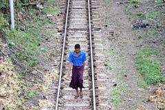 De dorpsbewoner die van de Myanmaresemens in korte kokert-shirt en Lange Yi op de spoorwegsporen lopen stock afbeeldingen
