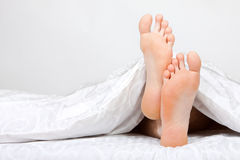 De dos pies en una cama Fotos de archivo libres de regalías