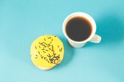 De doughnut en coffe vormt op blauwe achtergrond/Doughnut in geel glansdec tot een kom royalty-vrije stock afbeeldingen
