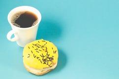 De doughnut en coffe vormt op blauwe achtergrond/Doughnut in gele die glans tot een kom met donkere chocoladestokken en coffe kop royalty-vrije stock afbeelding